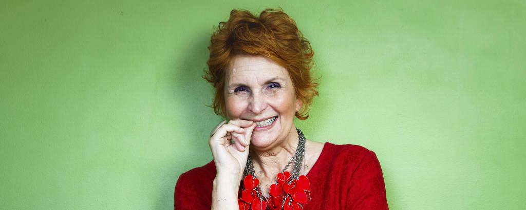 Mulher ruiva sorri, usando vestido vermelho