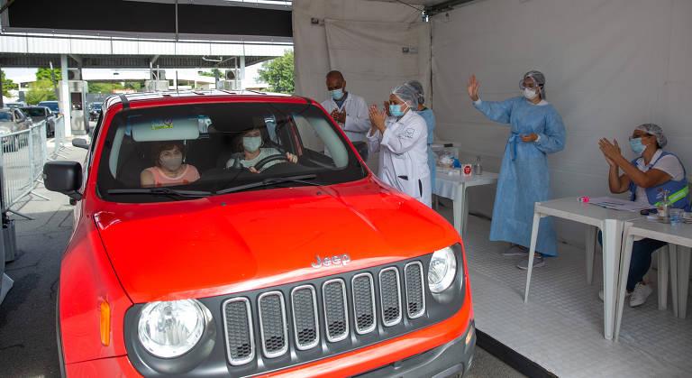 Duas pessoas dentro de um Jeep vermelho são atendidas por dois enfermeiros paramentados com equipamentos de segurança e máscaras