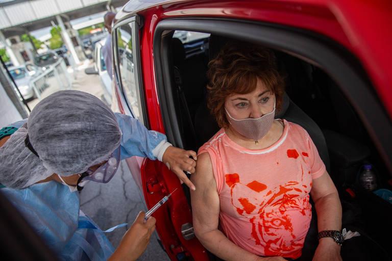 Idosa vestida com camiseta rosa estampada de vermelho é vacinada por enfermeira paramentada com touca, equipamento de segurança e máscara