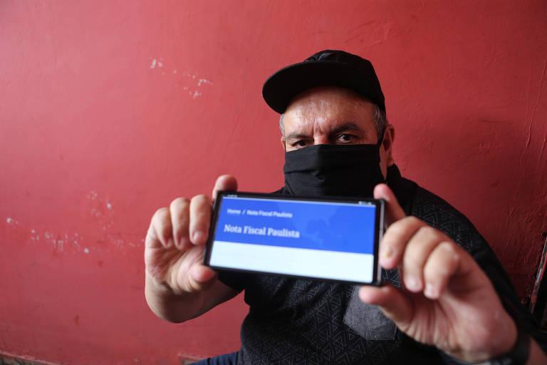 O segurança João Lopez, 62, mostra no celular aplicativo do Nota Fiscal Paulista; participante assíduo do programa, ele está deixando de pedir o CPF na nota após perceber que os créditos estão menores