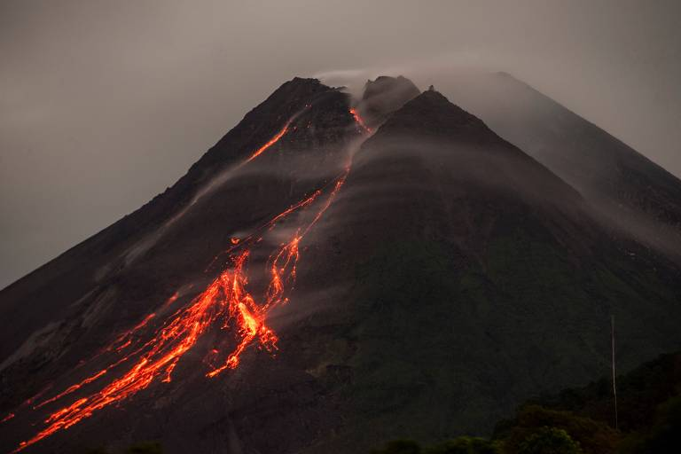 Imagem mostra pico de imensa montanha de cor escura, com material vulcânico de cor avermelhada escorrendo desde o topo.