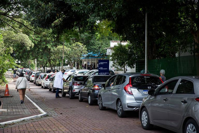 Fila de carros em rua arborizada. Uma pessoa de jaleco branco orienta um motorista.