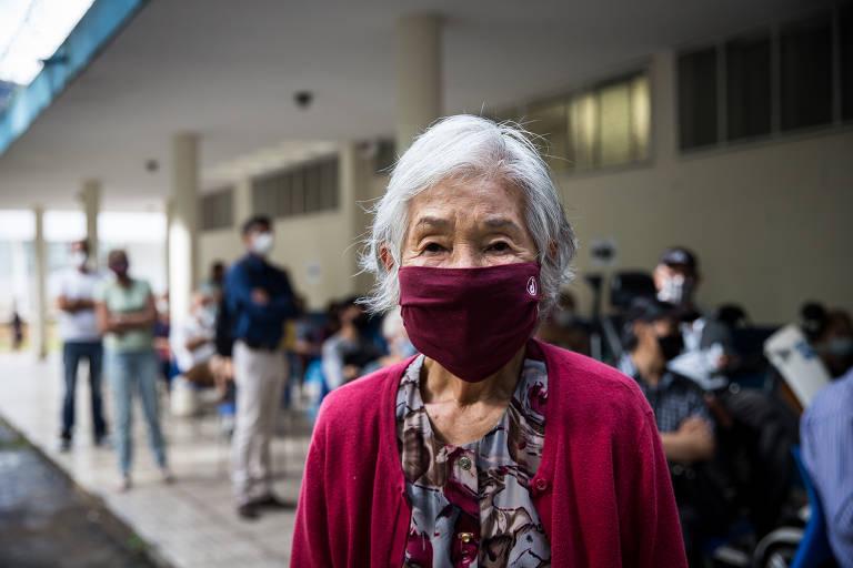 Mulher de cabelos brancos, blusa florida e máscara e casaco vermelhos em primeiro plano; ao fundo vê-se uma fila de pessoas em frente a um posto de saúde