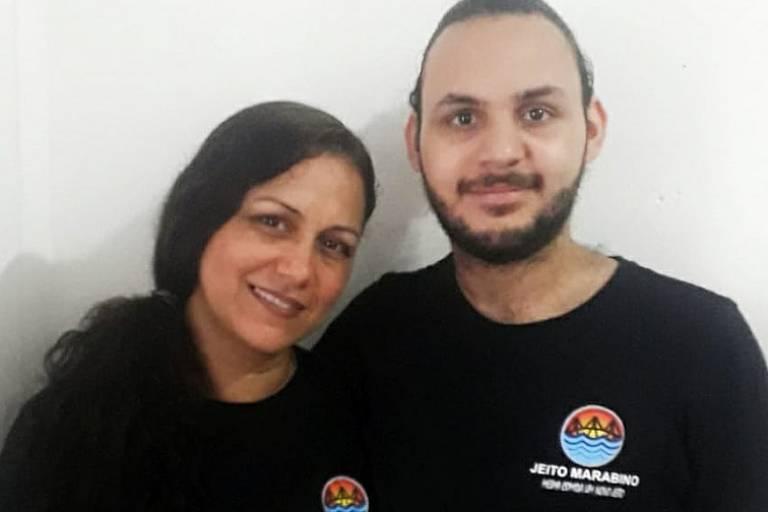 Homem branco de barba abraça mulher, que está à sua direita. Ambos usam camiseta preta.