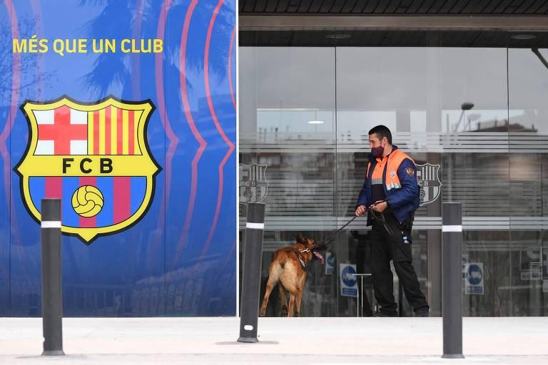 Um guarda com seu cão durante ação policial na sede do Barcelona, no Camp Nou
