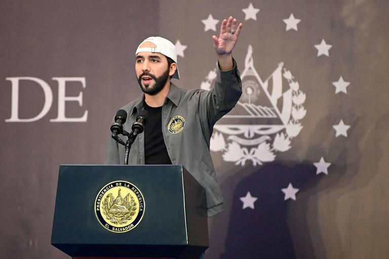 Nayib Bukele está com a mão esquerda para cima enquanto fala em um púlpito