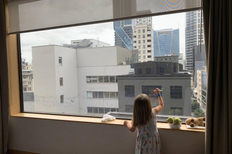Criança desenha em janela de quarto de hotel