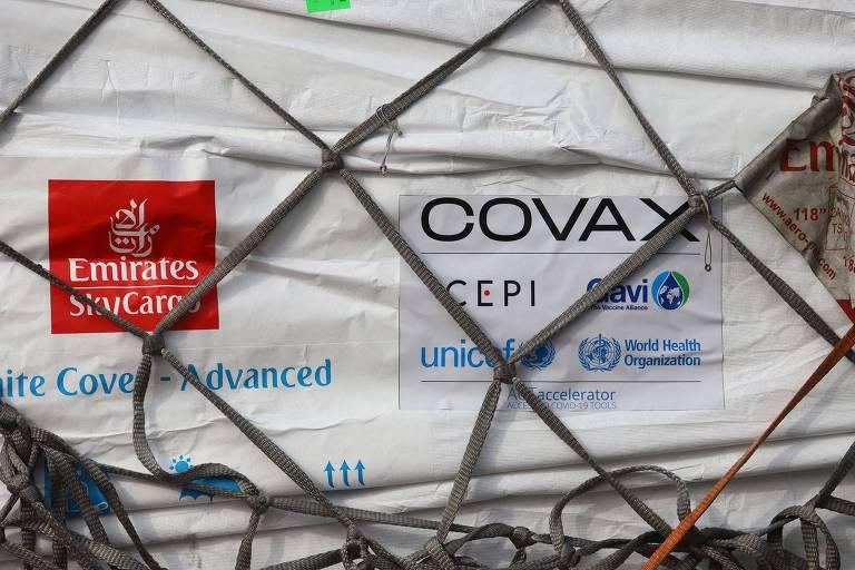 Contêiner branco preso por cordas, com cartaz onde está escrito Covax