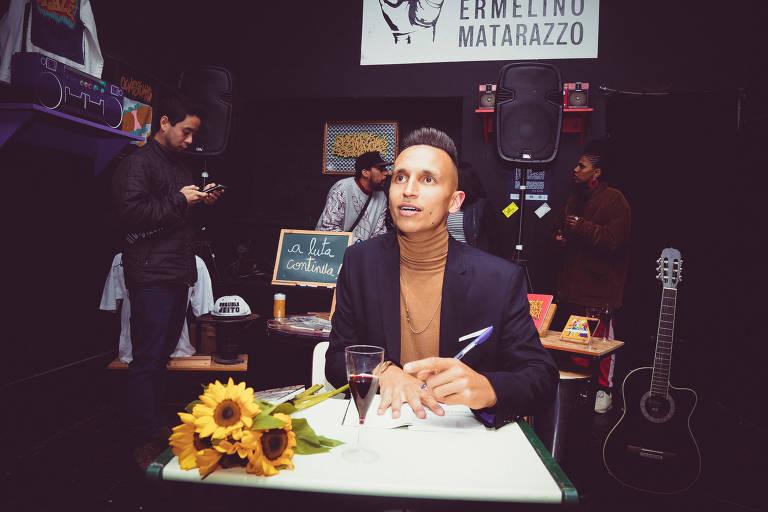 MC sentado em uma mesa com flor amarela em cima