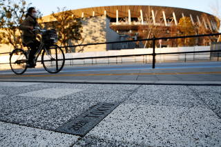 A woman cycles past a sign for Tokyo 2020 Olympic Games on the pavement in front of the National Stadium, the main stadium of Tokyo 2020 Olympics and Paralympics, in Tokyo
