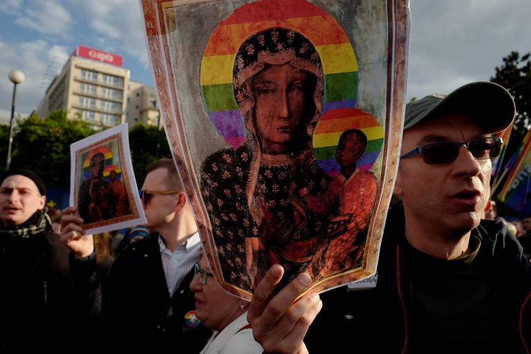 Manifestantes com cartazes de Nossa Senhora de Czestochowa sob o arco-íris LGBT