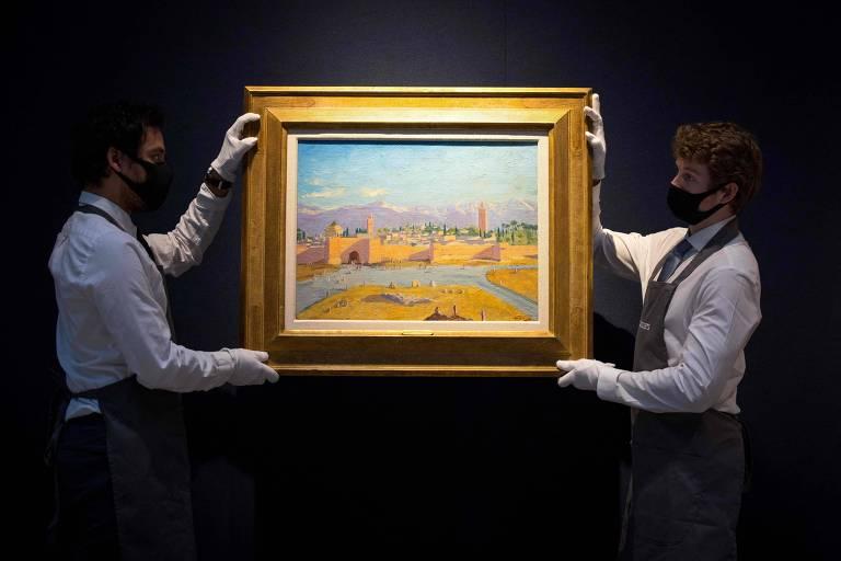 Dois homens brancos com máscara facial seguram uma pintura. No quadro, é possível ver uma paisagem