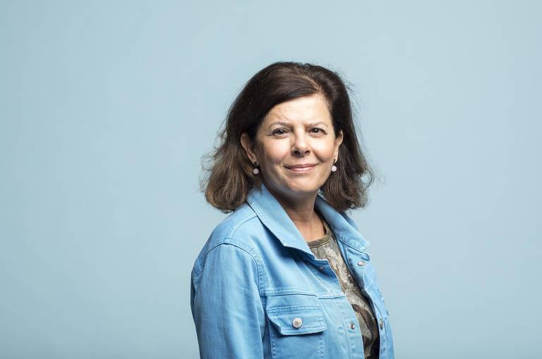 mulher branca de cabelos castanhos avermelhados veste jaqueta jeans e sorri para a câmera posando de perfil para a foto