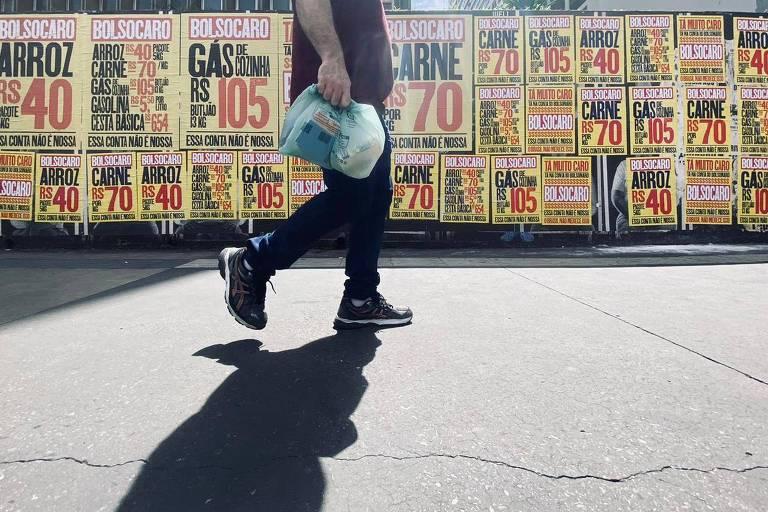 Um homem, que segura uma sacola, caminha em frente a cartazes amarelos