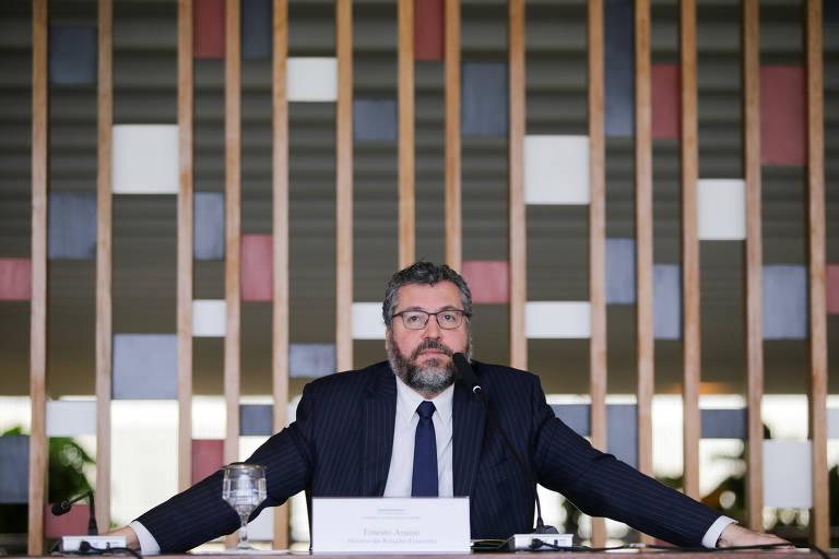 De terno e gravata, sentado em uma mesa e com os braços abertos, o ministro das Relações Exteriores, Ernesto Araújo, faz briefing à imprensa sobre temas da política externa brasileira