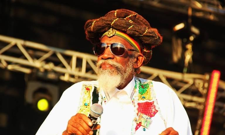 Homem negro idoso com roupas coloridas e óculos escuros cantando em palco