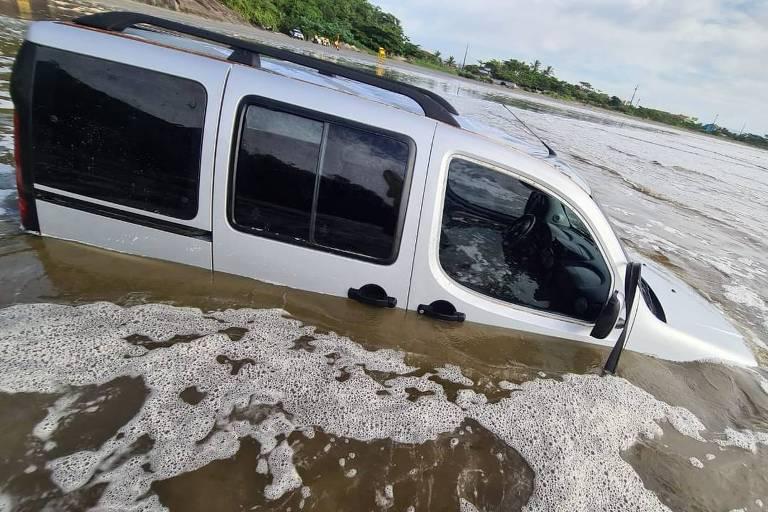 Carro emprestado é coberto por água em praia de Peruíbe