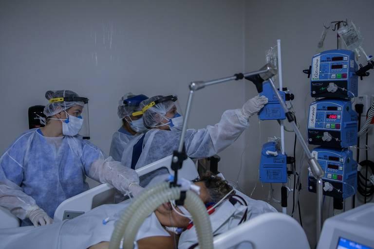 Funcionários paramentados cuidam de um paciente intubado em quarto de UTI.
