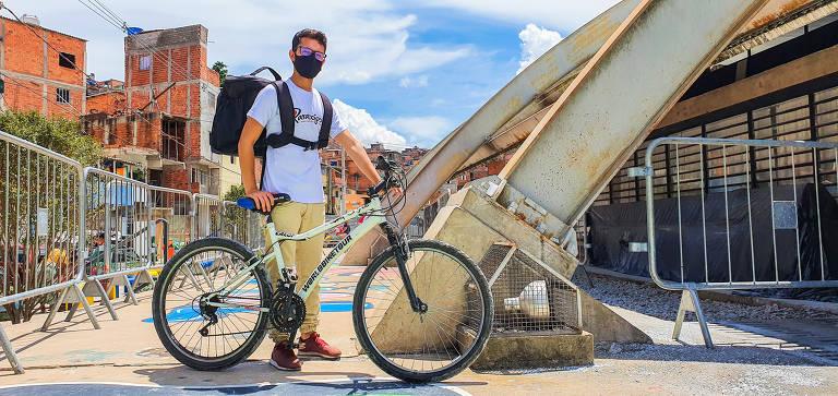 Jovem de máscara e mochila se apoia em sua bicicleta em frente à favela de Paraisópolis