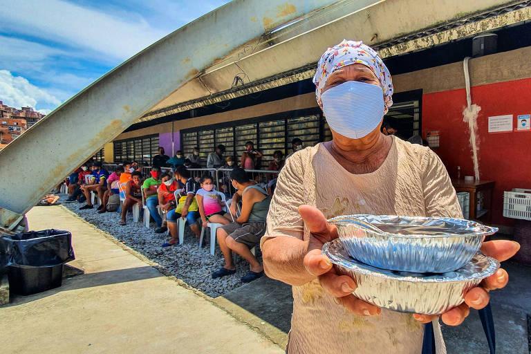 Moça entrega marmita em fila de pessoas que buscam refeições em Paraisópolis