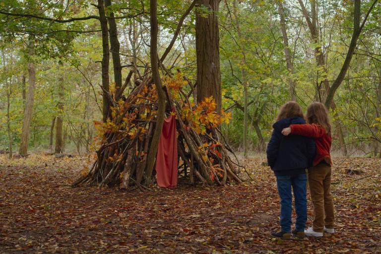 Duas meninas de oito anos de idade aparecem em uma floresta abraçadas. Elas estão de frente para uma cabana formada com troncos finos e galhos com folhas secas