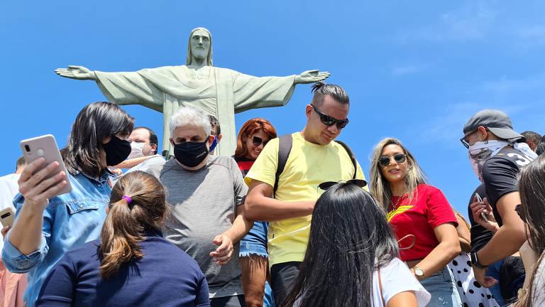 Várias pessoas de costas para o Cristo Redentor, algumas delas sem máscara