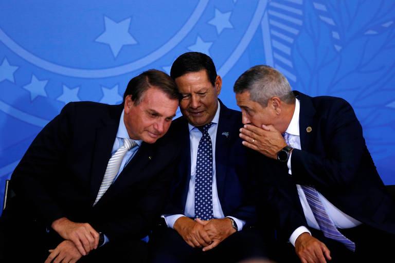 Braga Netto cochicha algo a Jair Bolsonaro e ao vice Hamilton Mourão, ao centro, em evento no Planalto