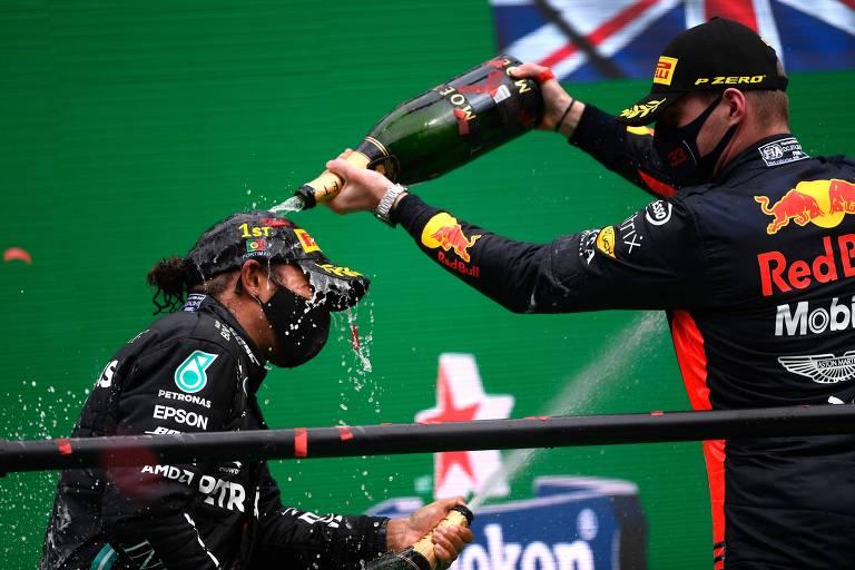 Lewis Hamilton (à esq.) recebe um banho de champagne de Max Verstappen após a vitória do britânico no GP de Portugal de 2020