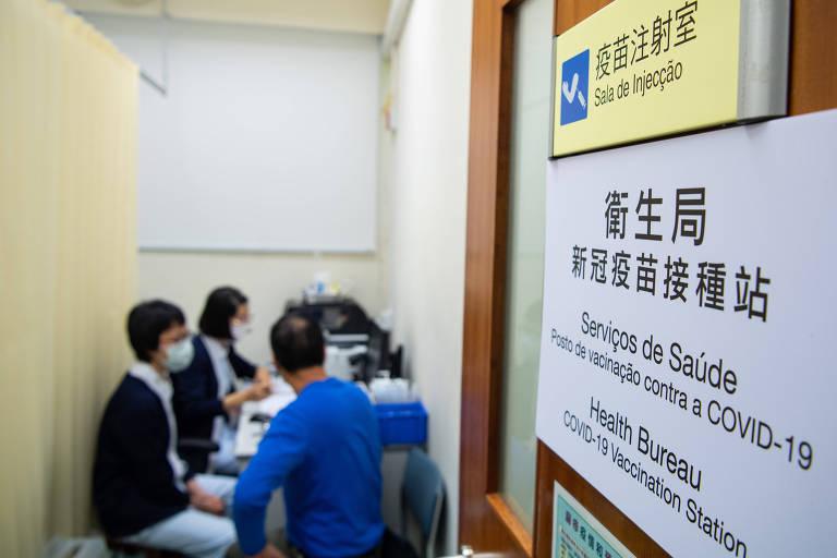 Foto mostra uma sala de vacinação em Macau, China, com duas mulheres que se preparam para vacina um homem. A porta de entrada tem inscrições em chinês e português.