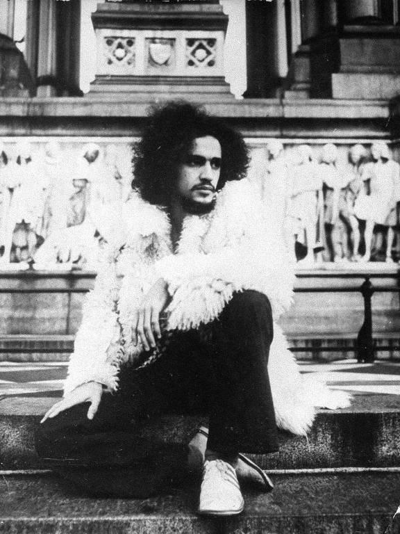 Caetano Veloso durante seu exílio em Londres, 1970; sentado em uma escada, músico veste casaco de pele branco