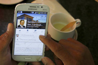 FILE PHOTO: A person uses a smartphone to look at the Facebook page of Cambodia's PM Hun Sen, at a restaurant in Phnom Penh
