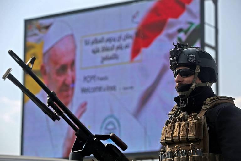 No primeiro plano, homem vestido com roupas camufladas e uma arma pesada; ao fundo, há um cartaz branco com a foto do papa Francisco e uma bandeira do Iraque