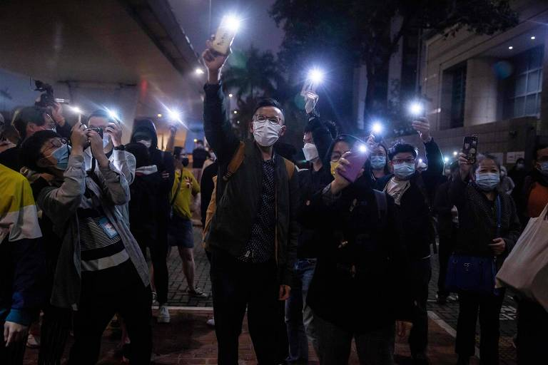 Apoiadores de ativistas pró-democracia presos em Hong Kong fazem ato em frente à corte onde ocorreu o julgamento