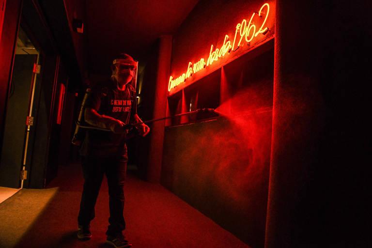 Homem com proteção facial espirra jato de álcool em parede, iluminada com luzes vermelhas