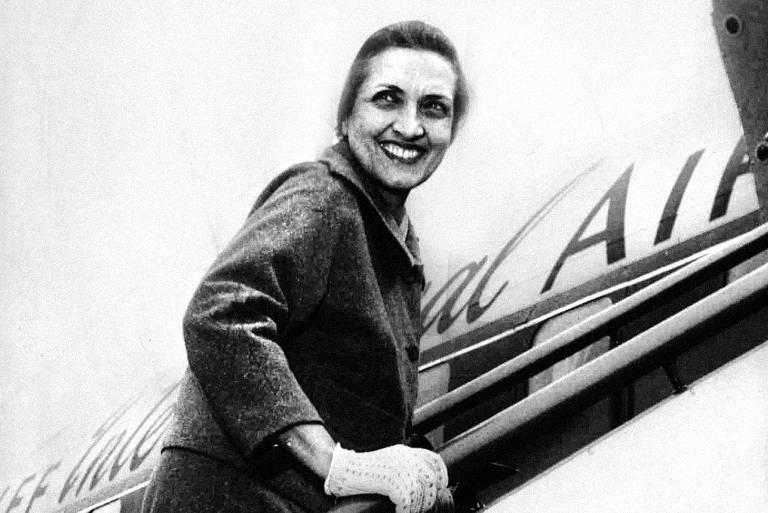 mulher branca sobe escada para entrar em avião enquanto sorri