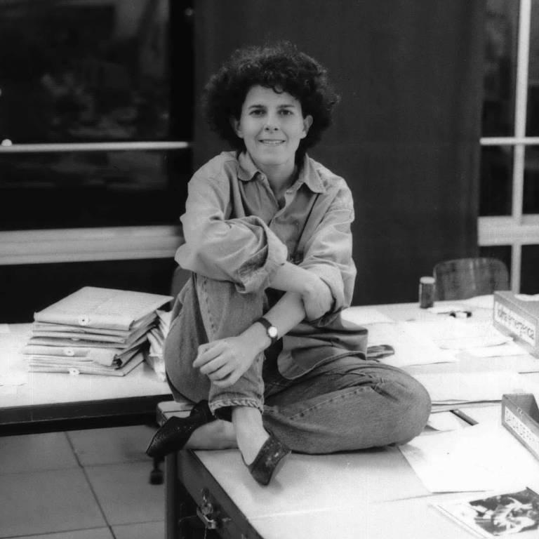 mulher branca de cabelos pretos cacheados sentada de pernas cruzadas em cima de uma mesa; ela sorri para a foto