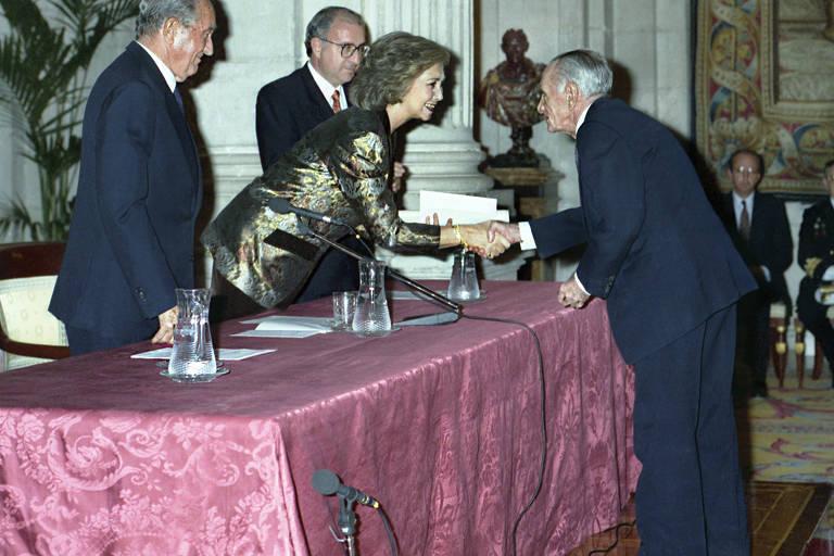 Na foto vê-se uma longa mesa coberta com um pano vinho-rosado; de um lado, a rainha Sofia, vestida com um blazer dourado, se inclina entre dois homens para dar a mão a João Cabral, de terno, bem velhinho, tinha 74 anos, que está do outro lado da mesa