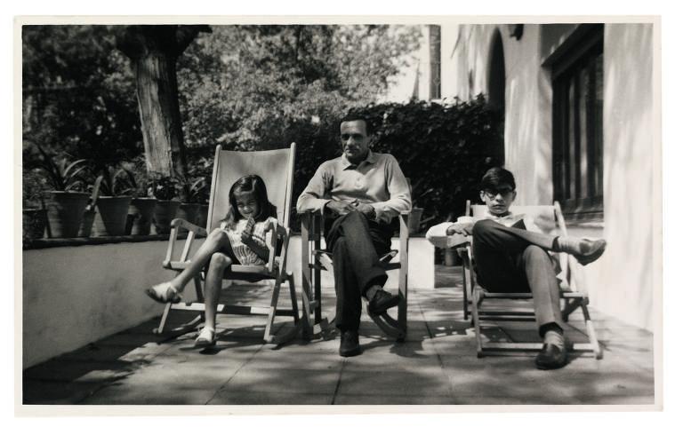 Foto preto e branco tirada numa varanda; na mureta há vasos com plantas, as crianças estão sentadas em espreguiçadeiras de madeira e o pai em uma cadeira, entre eles