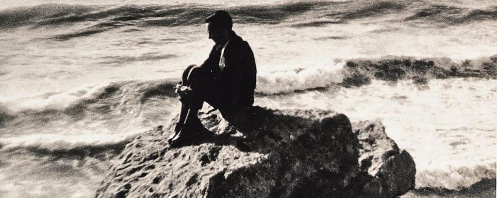 foto preto e branco, em tons de sépia, vertical, mostra o poeta sentado numa pedra, de frente para o mar que se estende em ondas até o fundo da imagem, sob um céu com nuvens luminosas