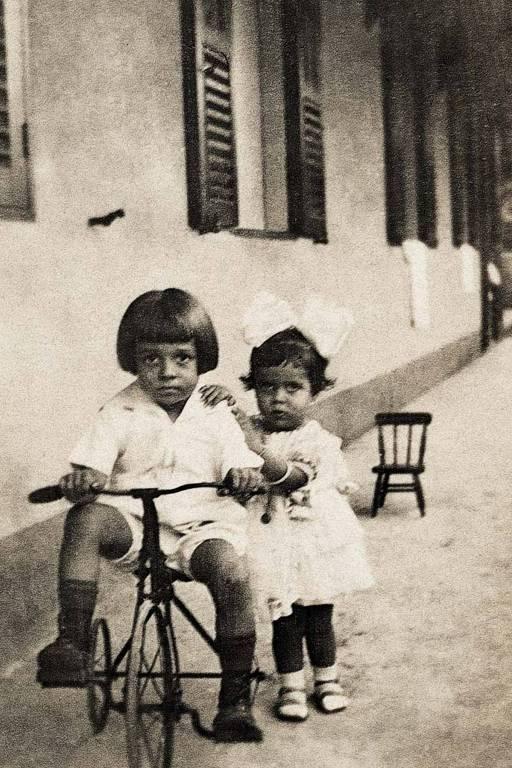 As crianças estão na varanda, ele num velocípede e ela apoiada no irmão; ao fundo há uma cadeirinha nfantil, a foto é preto e branco