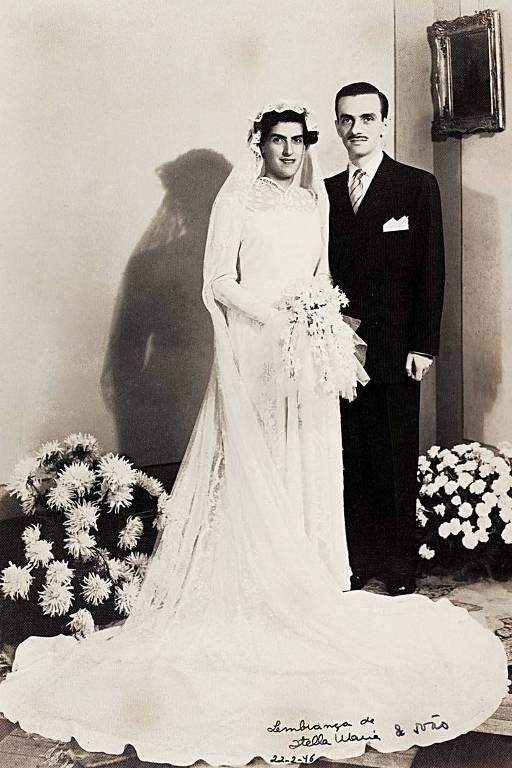 O casal posa para o retrato preto e branco, no qual ela aparece de noiva, com um vestido com cauda que se abre redonda aos seus pés, e ele de terno preto; de cada lado deles, um arranjo de flores no chão