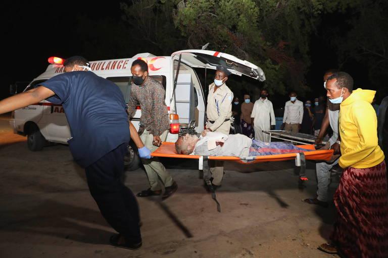 Pessoas ajudam uma pessoa ferida do lado de fora do Hospital de Madina após uma explosão num restaurante perto do porto de Mogadíscio