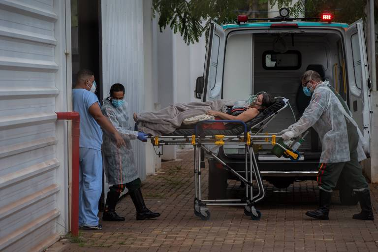 Mulher chega de ambulância em um hospital. Ela está deitada em uma maca e há enfermeiros em volta