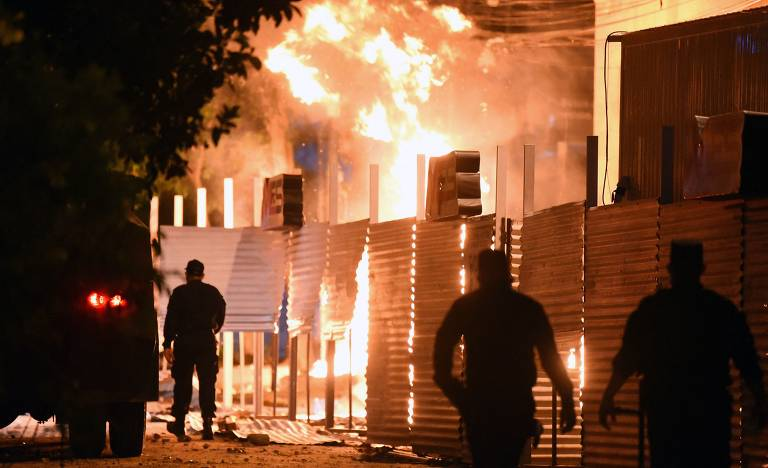 Policiais são vistos próximos a um incêndio provocado por manifestantes  na sede do Ministério do Comércio em Assunção