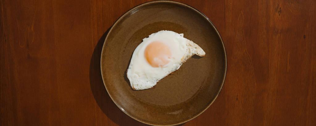um prato marrom com um ovo frito