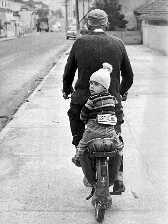 Criança sentada na garupa de bicicleta conduzida pelo avô, a caminho da creche