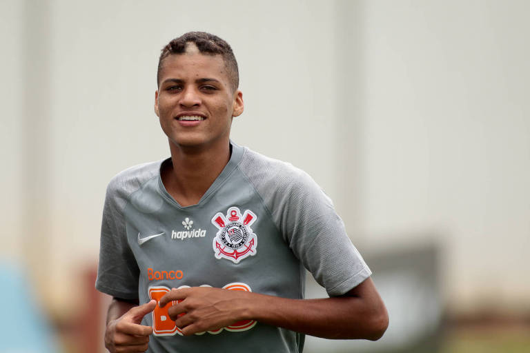 Homem negro de cabelos curtos sorrindo, vestindo camisa cinza do Corinthians, correndo.