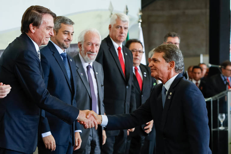 Silva e Luna cumprimenta Jair Bolsonaro; Bolsonaro está em local mais alto, e ambos estão de terno; ao lado de Bolsonaro estão outros presentes ao evento