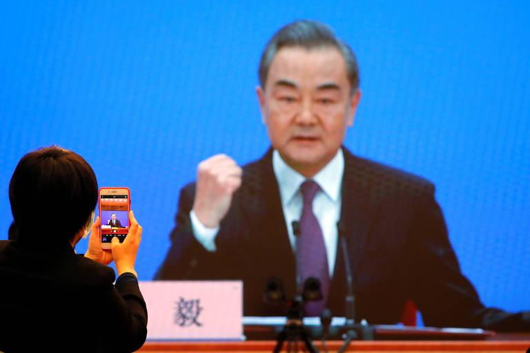 Repórter registra entrevista do chanceler Wang Yi em uma tela no Congresso Nacional do Povo, em Pequim