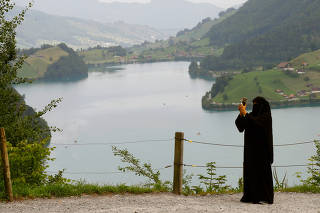 FILE PHOTO: A woman takes a picture from a lookout at Bruenigpass mountain pass road